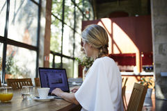 Ritratto di una studentessa che utilizza computer portatile portatile per la preparazione al coursework mentre sedendosi nella bi Fotografie Stock Libere da Diritti