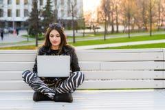 Ritratto di una studentessa felice che si siede sul banco con il computer portatile all'aperto e che esamina macchina fotografica Immagini Stock Libere da Diritti