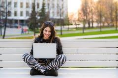 Ritratto di una studentessa felice che si siede sul banco con il computer portatile all'aperto e che esamina macchina fotografica Fotografia Stock
