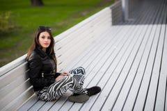 Ritratto di una studentessa felice che si siede sul banco con il computer portatile all'aperto e che esamina macchina fotografica Fotografia Stock Libera da Diritti