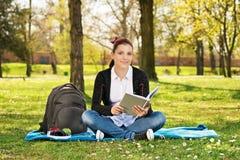 Ritratto di una studentessa in un parco che tiene un libro Immagini Stock