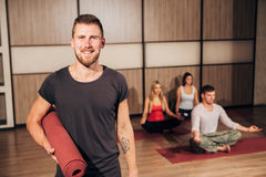 Ritratto di una stuoia e di sorridere di yoga della tenuta dell'uomo con la sua mano dietro la testa Immagini Stock Libere da Diritti