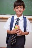 Ritratto di uno scolaro che tiene una mela Immagine Stock