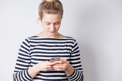 Ritratto di uno smartphone casuale sorridente della tenuta della donna sopra fondo bianco fotografia stock