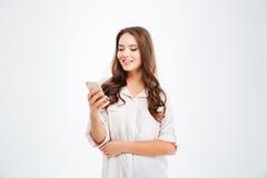 Ritratto di uno smartphone sorridente della tenuta della donna sopra fondo bianco Fotografia Stock Libera da Diritti