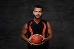 Ritratto di uno sportivo afroamericano Giocatore di pallacanestro in abiti sportivi con una palla Immagini Stock Libere da Diritti