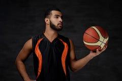 Ritratto di uno sportivo afroamericano Giocatore di pallacanestro in abiti sportivi con una palla Fotografia Stock Libera da Diritti