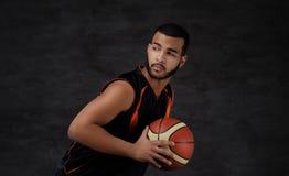 Ritratto di uno sportivo afroamericano Giocatore di pallacanestro in abiti sportivi con una palla Immagine Stock