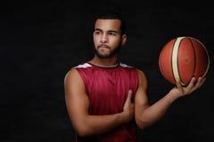 Ritratto di uno sportivo afroamericano Giocatore di pallacanestro in abiti sportivi con una palla Immagine Stock Libera da Diritti