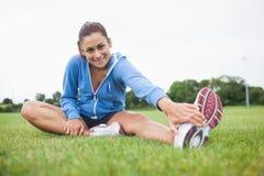 Ritratto di uno sportivo allungando la sua gamba sull'erba Immagini Stock Libere da Diritti