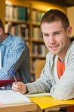 Ritratto di uno studente maschio sorridente allo scrittorio delle biblioteche Fotografie Stock Libere da Diritti