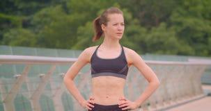 Ritratto di vista frontale del primo piano di giovane condizione femminile sportiva graziosa del pareggiatore in abiti sportivi s stock footage