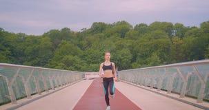 Ritratto di vista frontale del primo piano di giovane pareggiatore femminile sportivo grazioso che corre sul ponte in città urban video d archivio