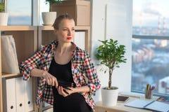 Ritratto di vista frontale di un architetto arredatore femminile che sta allo studio di arte, appoggiandosi gli scaffali per libr Immagine Stock
