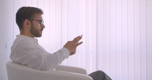 Ritratto di vista laterale del primo piano dell'uomo d'affari caucasico barbuto bello adulto in vetri facendo uso della compressa stock footage