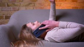 Ritratto di vista laterale del primo piano di giovane femmina castana caucasica attraente che ha una menzogne di telefonata rilas archivi video