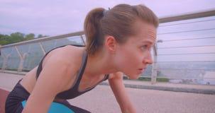 Ritratto di vista laterale del primo piano di giovane pareggiatore femminile sportivo caucasico sveglio che si siede in una posiz archivi video
