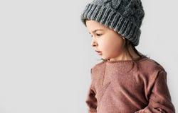 Ritratto di vista laterale della bambina sveglia nel cappello caldo di inverno isolato su un fondo bianco dello studio immagine stock