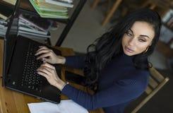 Ritratto di vista laterale della giovane donna che lavora al computer portatile al caffè Fotografie Stock Libere da Diritti