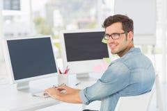 Ritratto di vista laterale di un artista maschio che per mezzo del computer Fotografie Stock