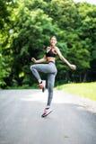 Ritratto di vista laterale di un ou di salto di esercizi di sport della donna di forma fisica fotografia stock libera da diritti