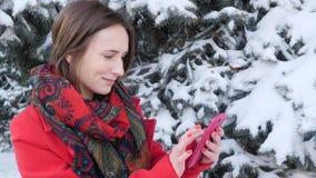 Ritratto di vista laterale di una donna emozionante che utilizza un telefono cellulare astuto nel parco nell'inverno Movimento le stock footage