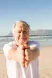 Ritratto di yoga di pratica attiva dell'uomo senior alla spiaggia Immagini Stock