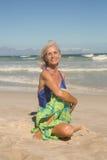 Ritratto di yoga di pratica sorridente della donna mentre sedendosi sulla sabbia Fotografia Stock
