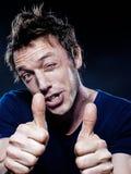 Ritratto divertente dell'uomo che sbatte le palpebre pollice in su Fotografia Stock Libera da Diritti