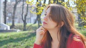 Ritratto divertente di giovane donna castana emozionale in camicia rossa con gli occhiali da sole in sua mano che esamina la macc archivi video