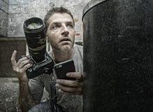 Ritratto divertente di stile di vita di giovane uomo del fotografo dei paparazzi nell'azione nascosto dietro gli appostamenti del immagine stock libera da diritti