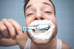Ritratto divertente di un uomo che pulisce i suoi denti con molta schiuma fotografia stock libera da diritti