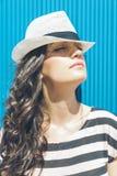 Ritratto elegante attraente della donna di estate sulla parete blu Fotografia Stock