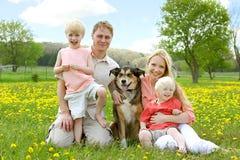 Ritratto felice della famiglia nel prato del fiore Fotografia Stock