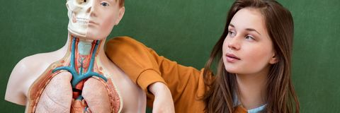Ritratto femminile fresco dello studente della High School con un modello artificiale del corpo umano Studente divertendosi nella immagini stock libere da diritti