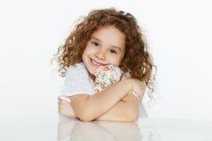 Ritratto frontale della bambina riccia sveglia allegra che abbraccia un giocattolo, messo alla tavola sopra fondo bianco Copi lo  fotografie stock libere da diritti
