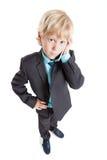Ritratto grandangolare del ragazzo abbastanza biondo in vestito e del legame che parlano dal cellulare, fondo bianco isolato Fotografia Stock