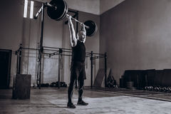 Ritratto integrale in bianco e nero dell'uomo forte che solleva un bilanciere durante l'allenamento del crossfit alla palestra Fotografia Stock Libera da Diritti