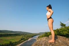Ritratto integrale dell'istruttore castana di forma fisica della donna con l'allungamento perfetto dell'ente muscolare all'aperto Fotografia Stock