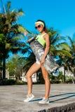 Ritratto integrale della donna abbronzata che posa con il longboard vicino alle palme in paese tropicale Immagini Stock Libere da Diritti