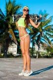 Ritratto integrale della donna abbronzata che posa con il longboard vicino alle palme in paese tropicale Immagini Stock