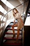 Ritratto integrale della donna bionda che porta un cappotto che posa provocatorio sui punti in un interno moderno. Bella donna in  fotografia stock libera da diritti