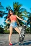 Ritratto integrale della donna che posa con il longboard vicino alle palme in paese tropicale Fotografia Stock