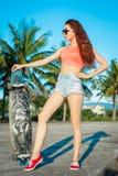 Ritratto integrale della donna che posa con il longboard vicino alle palme in paese tropicale Immagini Stock