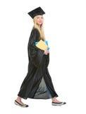 Giovane donna in abito di graduazione con il libro Immagine Stock