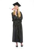 Giovane donna felice in abito di graduazione con il diploma Immagini Stock