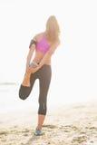 Ritratto integrale della giovane donna di forma fisica che allunga sulla spiaggia Immagine Stock