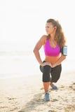 Ritratto integrale della giovane donna di forma fisica che allunga sulla spiaggia Fotografia Stock Libera da Diritti