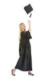 Giovane donna felice in protezione di lancio dell'abito di graduazione Immagini Stock