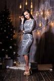 Ritratto integrale di bella donna castana sorridente in un vestito frizzante d'argento davanti all'albero Feste, nuovo anno, immagine stock